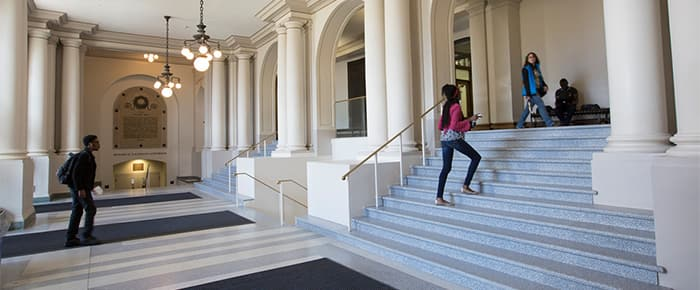 A student climbs the stairs to the first floor of Goldwin Smith Hall